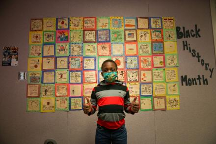 2nd gr. Horizon student gives the thumbs up in front of his class created Black History Month quilt