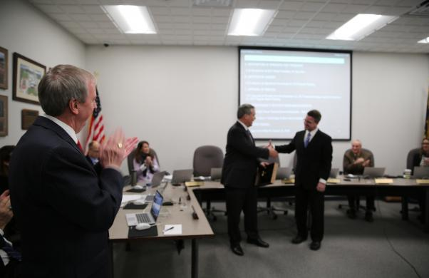 Dr. Thacker and Board Members applaud outgoing President Gary Fox as incoming President Chris Riley thanks him for his service