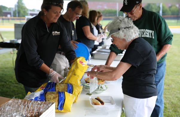 Asst. Supt. Heather Short assists a Penn Patron at the Community Tailgate