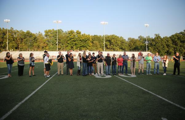 School board member Larry Beehler is recognized on the field during a pregame recognition ceremony